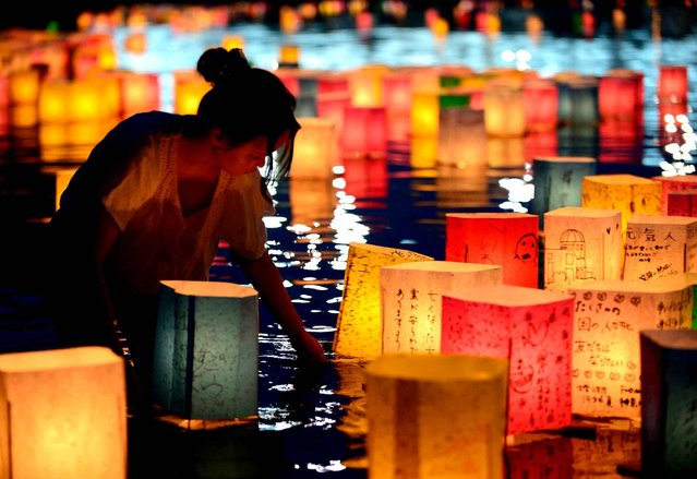 A woman tended paper lanterns, on August 6, 2013 that were lit in honor of victims of the 1945 atomic bombing of Hiroshima. (Photo by Shizuo Kambayashi/Associated Press)