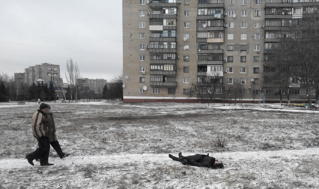 Residents pass by a dead body after an artillery strike in Kramatorsk, eastern Ukraine, Tuesday, February10, 2015. (Photo by AP Photo)