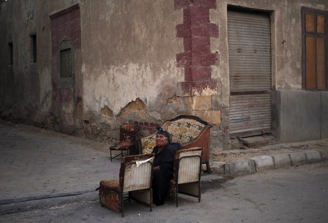 A woman sits on a chair in an alley inside the cemetery area where she lives east of Cairo, Egypt, September 6, 2015. (Photo by Asmaa Waguih/Reuters)