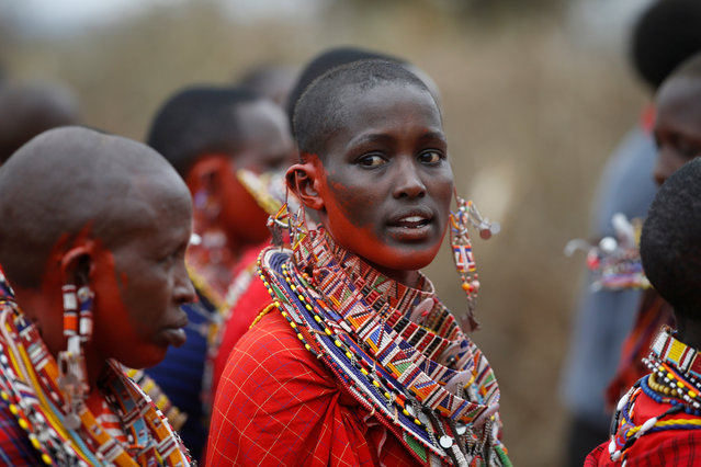 A Maasai woman painted with a red ochre pigment dances during an initiation into an age group ceremony near the town of Bisil, Kajiado county, Kenya on August 23, 2018. (Photo by Baz Ratner/Reuters)