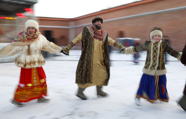 People dressed in traditional Russian clothes dance during the celebration of Orthodox Christmas in St.Petersburg, Russia, Thursday, January 7, 2016. Russian Orthodox believers celebrate Christmas by the Julian calendar on Jan. 7. (Photo by Dmitry Lovetsky/AP Photo)