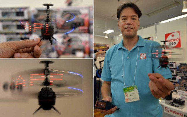 Japan's toy maker Kyosho employee displays the company's palm sized infrared controlled drone 'Neon Messenger', which can displays LED messages while flying at a toy trade show in Tokyo on September 11, 2013. Kyosho will put it on the market end of this month for the Christmas gift. (Photo by Yoshikazu Tsuno/AFP Photo)