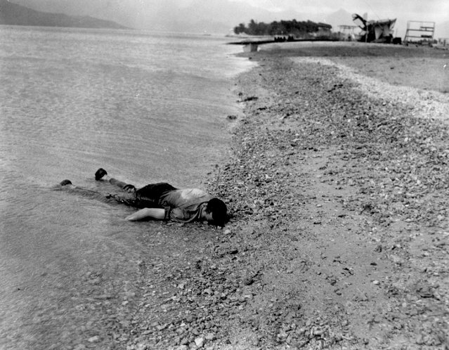 The body of a sailor killed during the Japanese air attack at Naval Air Station Kanoehe Bay lies on the shoreline, at Pearl Harbor, Hawaii, U.S. December 7, 1941. (Photo by Reuters/U.S. Navy/National Archives)