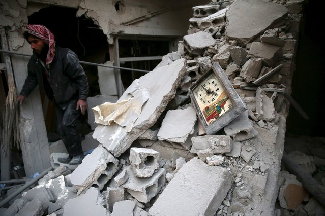 A man walks near a damaged clock in a site hit by what activists said were airstrikes carried out by the Russian air force in the town of Douma, eastern Ghouta in Damascus, Syria January 10, 2016. (Photo by Bassam Khabieh/Reuters)