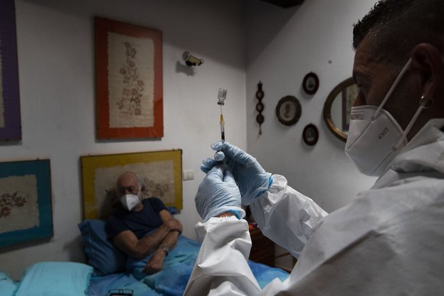 Nurse Luigi Lauri prepares a dose of the Pfizer vaccine for 85-year old Giorgio Tagliacarne at his home in Rome, Tuesday, April 27, 2021. The doctor and nurse manage just 12 shots day – six in the morning, six in the afternoon – making house calls to Rome's homebound elderly to administer coronavirus vaccines and along with them, the hope that Italy's most fragile might soon emerge from the pandemic. (Photo by Alessandra Tarantino/AP Photo)
