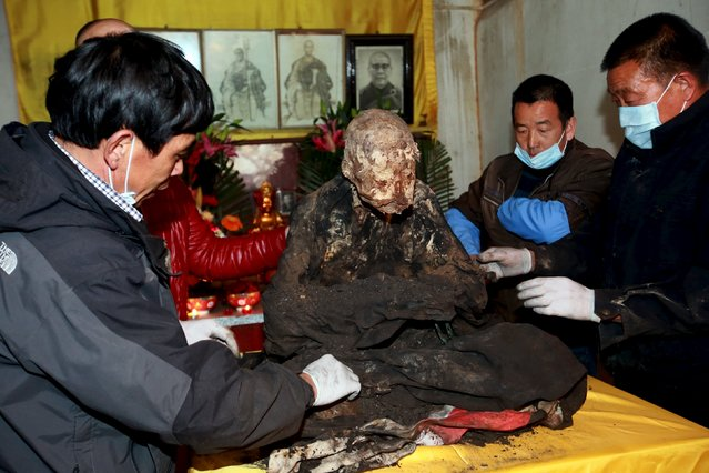 Workers remove charcoal and sandalwood debris from the mummified body of a monk during the unveiling ceremony at Puzhao temple, in Quanzhou, Fujian Province, China, January 10, 2016.  According to local media, the monk named Fuhou died three years ago at the age of 94 and his remains was placed in a vat and turned into a mummy as a sign of respect. (Photo by Reuters/Stringer)