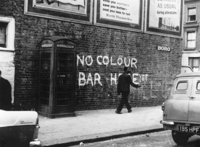"""A black man walking down a Notting Hill Street, where race riots had recently taken place, circa 1959. The graffiti behind him reads, """"No Colour Bar Here – Yet"""". (Photo by Keystone/Getty Images)"""