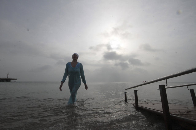 A woman walks out of cold waters of the Black Sea during Orthodox Epiphany celebrations in the port city of Yevpatoriya, Crimea, January 19, 2016. (Photo by Pavel Rebrov/Reuters)