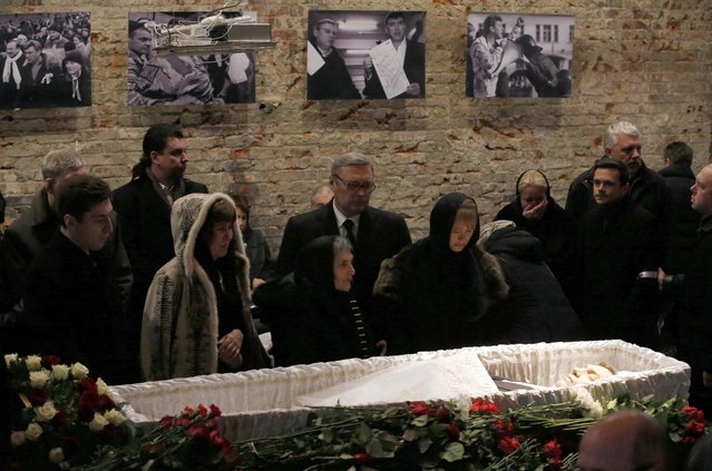 Mourners, including Dina Eidman (3rd L, front), mother of Russian leading opposition figure Boris Nemtsov, and Mikhail Kasyanov (C, back), an opposition leader and former Russian prime minister, attend a memorial service before the funeral of Nemtsov in Moscow, March 3, 2015. Several hundred Russians, many carrying red carnations, queued on Tuesday to pay their respects to Boris Nemtsov, the Kremlin critic whose murder last week showed the hazards of speaking out against Russian President Vladimir Putin. REUTERS/Maxim Zmeyev