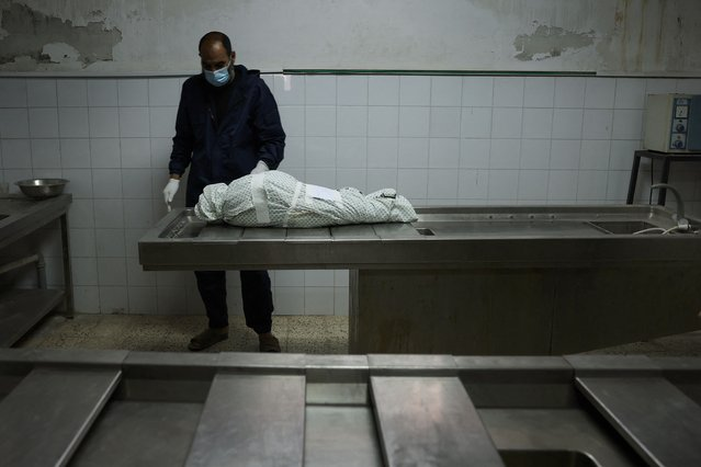 A Palestinian man stands by the body of Menna Shreir, 3, on May 19, 2021 at a morgue in Gaza City, after she died of her injuries following an Israeli air strike. The parentns of the three-year-old girl, who died of her wounds on May 19, 2021, were killed in the air strike on their home in Gaza City last week. (Photo by Mohammed Abed/AFP Photo)