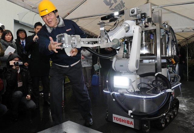 An engineer of Toshiba displays a decontamination robot, for work inside a nuclear plant, during a demonstration at Toshiba's technical center in Yokohama, suburban Tokyo on February 15, 2013. The crawler robot blasts dry ice particles against contaminated floors or walls and will be used for the decontamination in TEPCO's stricken Fukushima nuclear power plant. (Photo by Yoshikazu Tsuno/AFP Photo)