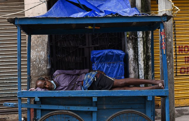 A street vendor sleeping in his mobile stall, during lockdown due to COVID-19 coronavirus pandemic, in Guwahati, India on 05 June 2021. India reported 120529 new Covid-19 cases on Saturday, its lowest daily spike since April 7. (Photo by David Talukdar/NurPhoto/Rex Features/Shutterstock)