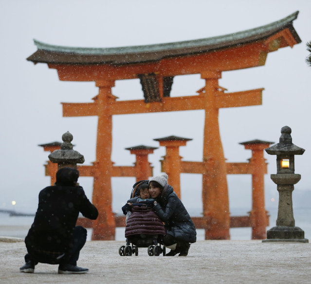 In this Sunday, January 24, 2016 photo, a family takes a souvenir photo in snow in front of the grand Torii gate, standing in the sea water, of the Itsukushima Shrine in Miyajima island in Hatsukaichi, Hiroshima, western Japan. Heavy snow in western and central Japan left several people dead in Japan over the weekend. (Photo by Shohei Miyano/Kyodo News via AP Photo)