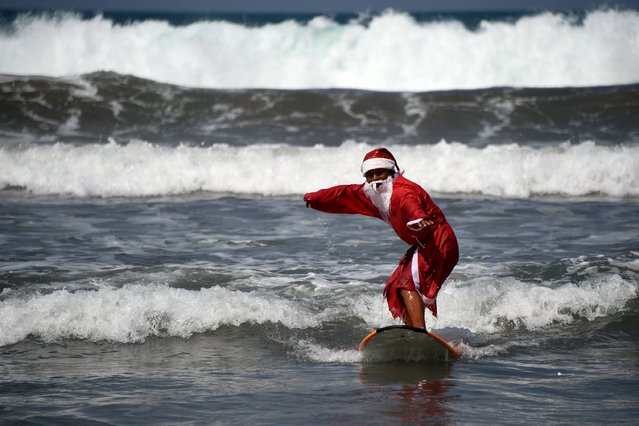 A surfer dressed in a Santa Claus outfit surfs on Kuta beach on Indonesia's resort island of Bali on December 19, 2016. The popular resort island, a pocket of Hindu culture in a country with the biggest Muslim population in the world, receives thousands of tourists every year over the Christmas season. (Photo by Sonny Tumbelaka/AFP Photo)