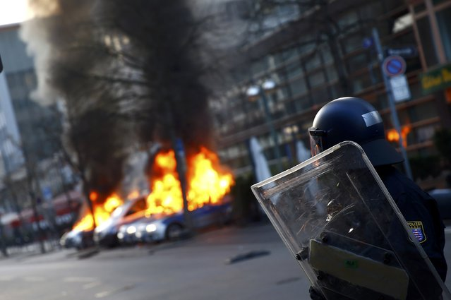 A policeman looks on as German police cars, set on fire by anti-capitalist protesters, burn near the European Central Bank (ECB) building before the official opening of its new headquarters in Frankfurt March 18, 2015. (Photo by Kai Pfaffenbach/Reuters)