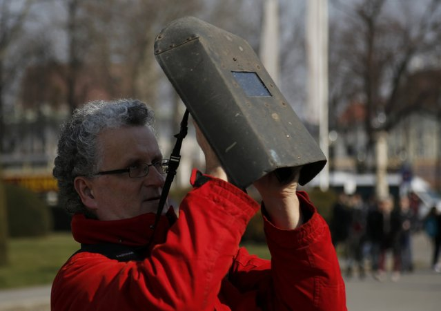 A man uses a welding face mask to observe a partial solar eclipse in Viennaa March 20, 2015. (Photo by Leonhard Foeger/Reuters)