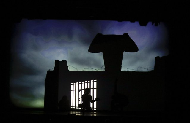 """In this photo taken on Tuesday, December 20, 2016, dancers of the U.S. company """"Catapult"""" create a jail, during their show """"Magic Shadows"""", in Milan, Italy. (Photo by Luca Bruno/AP Photo)"""