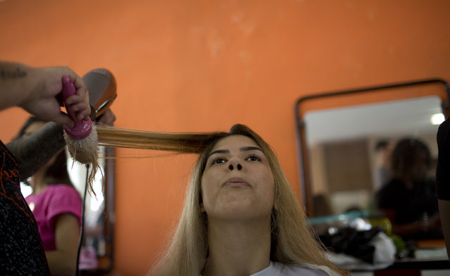 A hairstylist blow drys the hair of an inmate in preparation for the 13th annual Miss Talavera Bruce beauty pageant at the penitentiary the pageant is named for, in Rio de Janeiro, Brazil, Tuesday, December 4, 2018. Hairdressers and makeup artists volunteer their time to ready the contestants who are judged on their beauty, appeal and attitude. (Photo by Silvia Izquierdo/AP Photo)