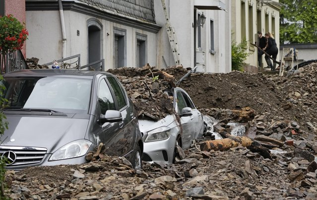 """Cars are covered in Hagen, Germany, Thursday, July 15, 2021 with the debris brought by the flooding of the """"Nahma"""" river the night before. People have died and dozens of people are missing in Germany after heavy flooding turned streams and streets into raging torrents, sweeping away cars and causing some buildings to collapse. (Photo by Martin Meissner/AP Photo)"""