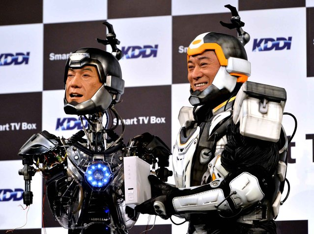 """Japanese actor Ken Matsudaira (R), clad in a robot suit, smiles with an android robot (L) in his likeness called """"Real Android Matsuken"""" at a press presentation in Tokyo on November 19, 2013. The android robot was developed for an advertisement for Japanese telecom company KDDI. (Photo by Yoshikazu Tsuno/AFP Photo)"""
