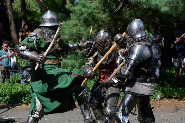 """Members of the """"Gladiators NYC"""" armored combat group fight in Central Park, New York on July 10, 2021. Once a month a bucolic corner of New York's Central Park becomes an impromptu battlefield as combatants in full medieval armour vie before baying picnickers and passersby, in a demonstration of brute strength and swordsmanship. (Photo by Ed Jones/AFP Photo)"""