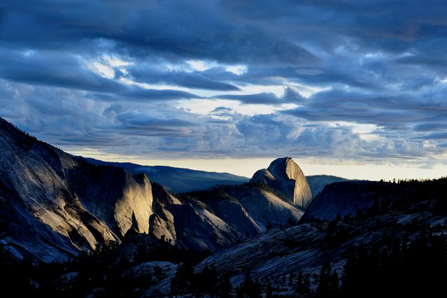"""Last Light on Half Dome"". The sun had dipped below the clouds but still above the horizon, painting the face of Half Dome and the walls of Tenaya Canyon with amazing light. Photo location: Olmsted Point, Yosemite National Park, California. (Photo and caption by Douglas Croft/National Geographic Photo Contest)"