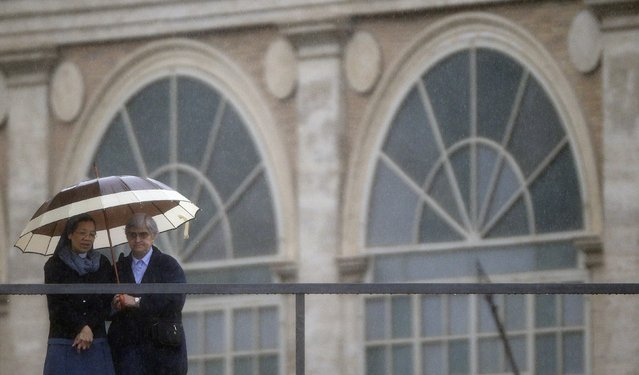 A nun stands under a umbrella in St. Peter's square before Pope Francis leads the Easter mass at the Vatican April 5, 2015. (Photo by Max Rossi/Reuters)