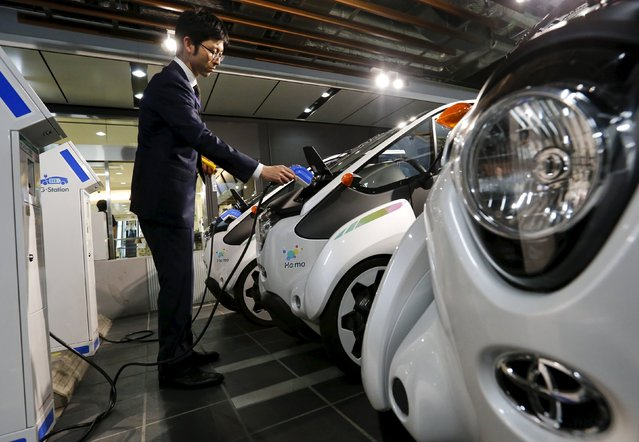 A staff member plugs a charger cable into Toyota's i-Road electric vehicle in Tokyo April 9, 2015. (Photo by Thomas Peter/Reuters)