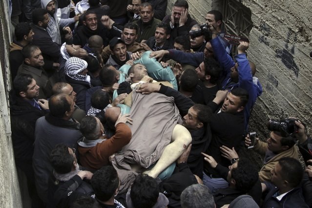 Mourners carry the body of Ziyad Awad during his funeral in Beit Ummar, West Bank, Friday, April 10, 2015. Awad was killed in clashes with Israeli soldiers, following the funeral of his cousin who died three months after being released from an Israeli jail. (Photo by Mahmoud Illean/AP Photo)