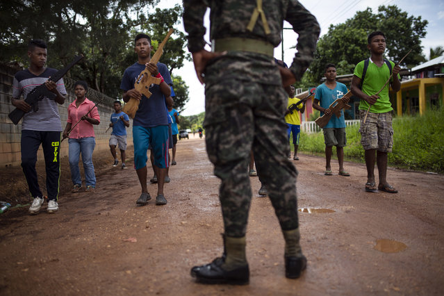 In this September 5, 2018 photo, supervised by a Honduran Army soldier, students practice their routine they plan to perform in an independence military parade, in Puerto Lempira, Honduras. (Photo by Rodrigo Abd/AP Photo)