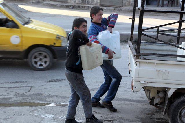 Residents carry water containers after filling them in Bab Neirab, Aleppo, Syria February 15, 2016. (Photo by Abdalrhman Ismail/Reuters)