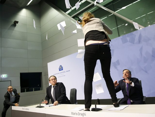 A protester jumps on the table in front of the European Central Bank President Mario Draghi during a news conference in Frankfurt, April 15, 2015. (Photo by Kai Pfaffenbach/Reuters)