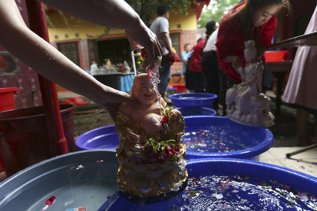 In this Wednesday, January 30. 2019, photo, a statue of a Chinese god is washed by in preparation for the Lunar New Year celebrations at a temple outside Jakarta, Indonesia. People of Chinese descent in the world's most populous Muslim country are preparing to celebrate the Lunar New Year of the Pig on Feb. 5. (Photo by Tatan Syuflana/AP Photo)