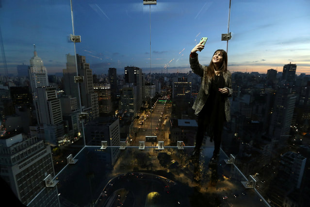 Influencer takes a selfie inside Sampa Sky, a reinforced glass box that protrudes beyond the building and allows to see not only the horizon, but also the ground below your feet, in downtown Sao Paulo, Brazil, August 3, 2021. (Photo by Amanda Perobelli/Reuters)