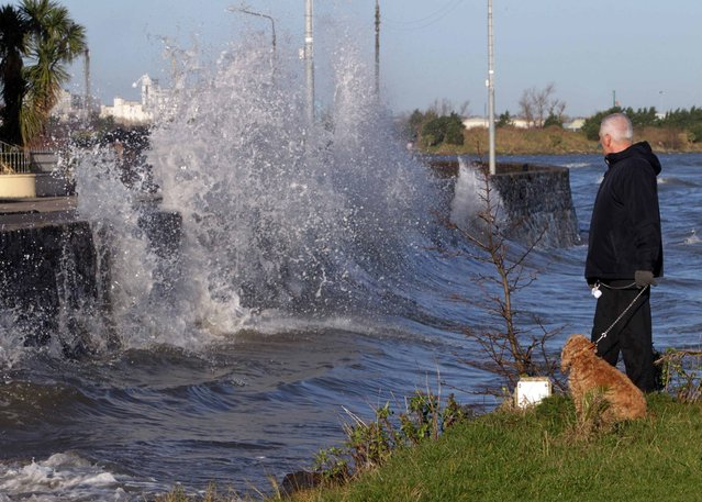 Pictured is Richard Finnegan from Sandymount watching the waves crashing against the wall along Sandymount Strand, Dublin, on January 1, 2013. Strong winds and heavy rain will return later today with warnings of high tides. (Photo by Mark Stedman/Photocall Ireland)
