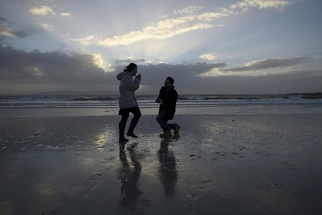 Stephen Donnellan from Galway (R) proposes to his girlfriend Julee Range, from the U.S., on a windy Silverstrand Beach, in Galway, Ireland December 23, 2016. The couple, who have been together for five years and live and work in China, arrived back in Donnellan's hometown on Friday, where he subsequently proposed. His proposal of marriage was accepted. (Photo by Clodagh Kilcoyne/Reuters)