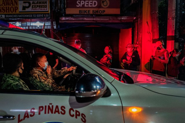 A police officer reminds people queuing for a COVID-19 vaccine to observe social distancing, outside a vaccination site on August 08, 2021 in Las Pinas, Metro Manila, Philippines. As a strict lockdown is reimposed in parts of the Philippines to curb the spread of the more contagious Delta variant of the coronavirus, Filipinos are defying curfew measures and flocking by the thousands to vaccination sites as early as midnight in hopes of getting vaccinated against COVID-19. The desperation comes after recent reports circulated that the government will not extend financial aid to unvaccinated individuals. While the presidential spokesperson denied this, President Rodrigo Duterte himself during one of his televised speeches that he will order police to jail unvaccinated individuals. (Photo by Ezra Acayan/Getty Images)