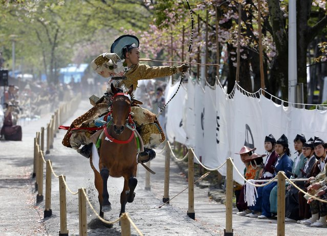 An archer in a samurai warrior costume aims at a target in the Asakusa Yabusame horseback archery event at Sumida Park in Tokyo, Saturday, April 18, 2015. (Photo by Shizuo Kambayashi/AP Photo)