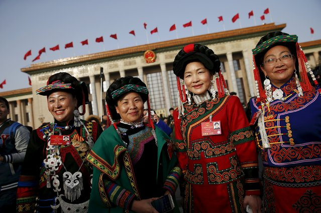 Ethnic minority delegates pose for pictures outside the Great Hall of the People ahead of the opening session of the National People's Congress (NPC) in Beijing, China, March 5, 2016. (Photo by Damir Sagolj/Reuters)