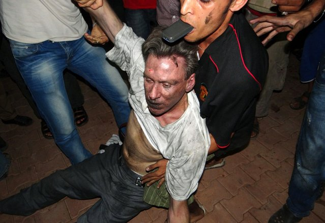 Libyan civilians help an unconscious man, identified by eyewitnesses as US ambassador to Libya Chris Stevens, at the US consulate compound in Benghazi in the early hours of September 12, 2012, following an overnight attack on the building. (Photo by AFP Photo/STR)