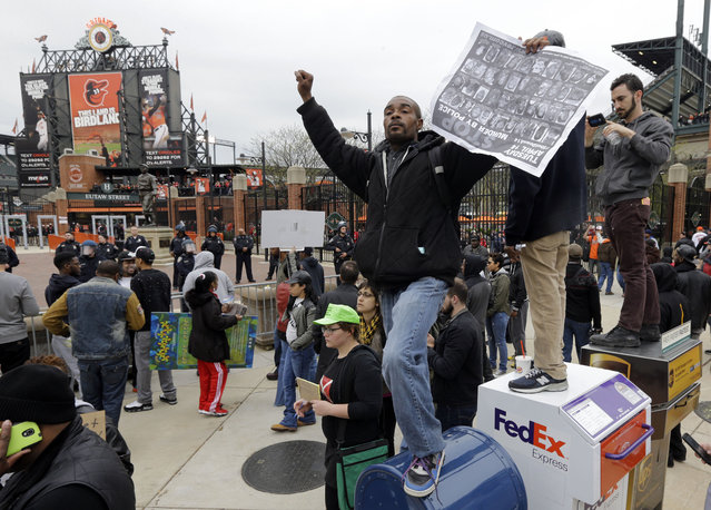 A protestor stands on a mailbox outside of Oriole Park at Camden Yards before a baseball game between the Boston Red Sox and the Baltimore Orioles after a rally for Freddie Gray, Saturday, April 25, 2015, in Baltimore. (Photo by Patrick Semansky/AP Photo)