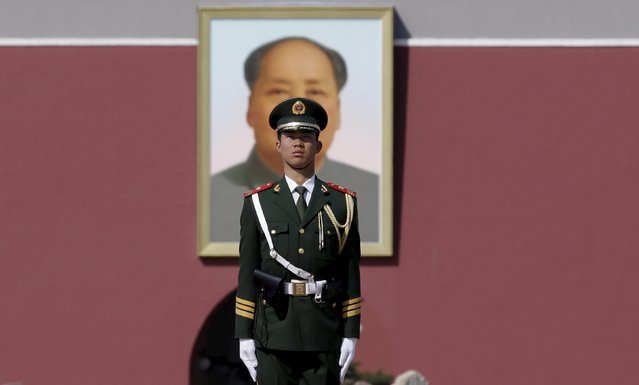 A Paramilitary policeman stands guard in front of a giant portrait of China's late Chairman Mao Zedong on the Tiananmen Gate ahead of the second plenary session of the National People's Congress (NPC) in Beijing, China March 9, 2016. (Photo by Jason Lee/Reuters)