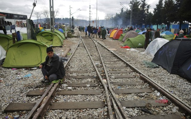 A migrant sits on railway tracks at a makeshift camp on the Greek-Macedonian border near the village of Idomeni, Greece March 10, 2016. (Photo by Stoyan Nenov/Reuters)