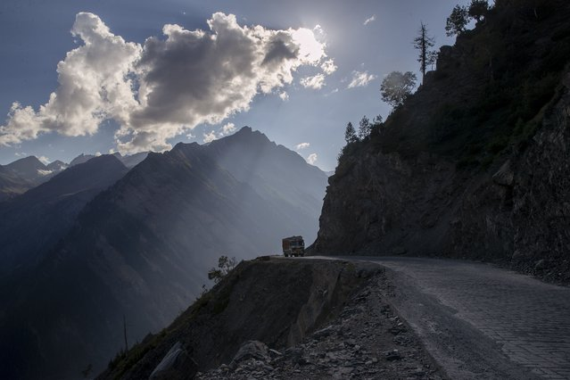 A lone truck travels on the Zojila Pass, northeast of Srinagar, Indian controlled Kashmir, Monday, September 27, 2021. High in a rocky Himalayan mountain range, hundreds of people are working on an ambitious project to drill tunnels and construct bridges to connect the Kashmir Valley with Ladakh, a cold-desert region isolated half the year because of massive snowfall. The $932 million project's last tunnel, about 14 kilometers (9 miles) long, will bypass the challenging Zojila pass and connect Sonamarg with Ladakh. Officials say it will be India's longest and highest tunnel at 11,500 feet (3,485 meters). (Photo by Dar Yasin/AP Photo)