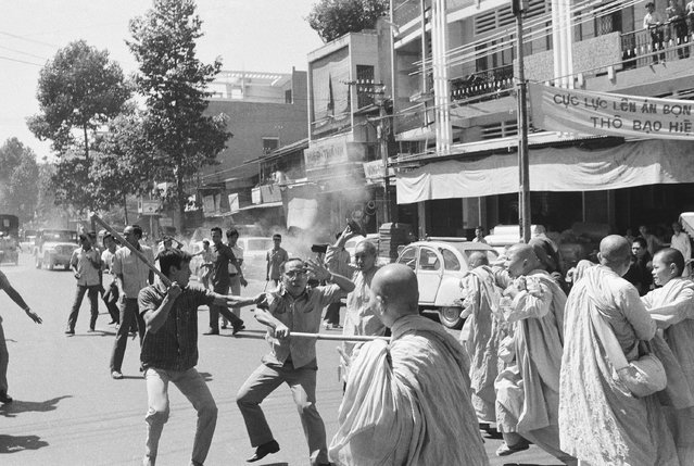 Two stick-wielding plainclothes policemen fight South Vietnamese Buddhist nuns in Saigon, Sunday, Jan. 26, 1975 during anti government demonstration. Officer (left) warns comrade that nun (background) is about to hit him with sandal. Melee occurred following political convention at pagoda. (Photo by Nguyen Tu A/AP Photo)