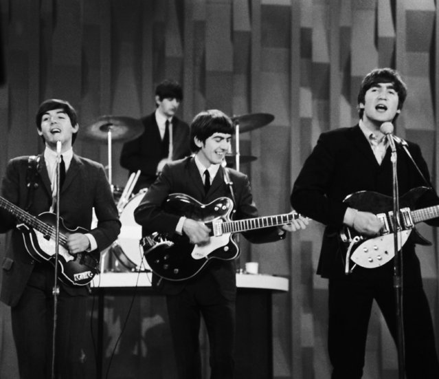 "In this February 9, 1964 file photo, The Beatles perform on the CBS ""Ed Sullivan Show"" in New York. Ringo Starr plays drums, rear, and playing guitars from left are Paul McCartney, George Harrison and John Lennon. An estimated 73 million Americans tuned in, the largest ever for a TV show at the time, or three times the amount of people who watched the latest ""American Idol"" finale, according to the Nielsen Co. (Photo by Dan Grossi/AP Photo)"