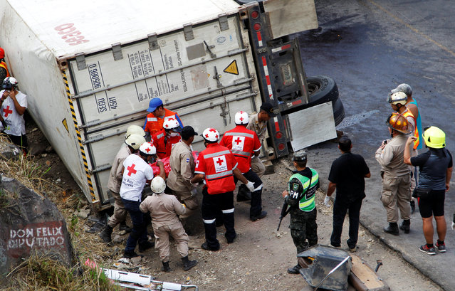 Rescue workers and members of the red cross are carrying a body after a crash between a bus and a truck on the outskirts of Tegucigalpa, Honduras, February 5, 2017. (Photo by Jorge Cabrera/Reuters)