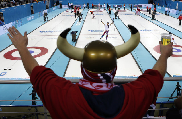 Norway's skip Thomas Ulsrud acknowledges the cheers of fan Rune Eikeland during men's curling competition against China at the 2014 Winter Olympics, Friday, February 14, 2014, in Sochi, Russia. (Photo by Robert F. Bukaty/AP Photo)
