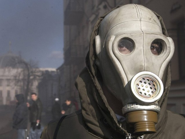 An anti-government protester wears a gas mask during clashes with Interior Ministry members in Kiev. Several thousand anti-government protesters clashed with police near Ukraine's parliament torching vehicles and hurling stones in the worst violence to rock the capital Kiev in more than three weeks. (Photo by Reuters/Stringer)