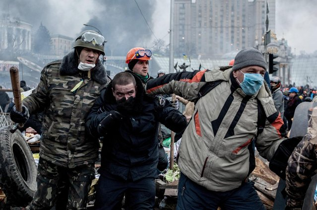 Anti-government demonstrators escort a captured police officer during clashes in Kiev, Ukraine, on February 20, 2014. (Photo by Yevgeny Maloletka/EPA)